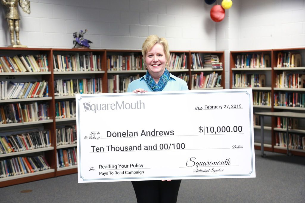 Pays to Read Winner holding a large check